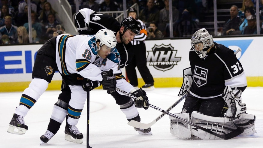 Los Angeles Kings goalie Jonathan Quick (32) stops a shot attempt by San Jose Sharks center Patrick Marleau (12) as defenseman Robyn Regehr, center, closes in during the first period of an NHL hockey game in San Jose, Calif., Tuesday, April 16, 2013. (AP Photo/Marcio Jose Sanchez)
