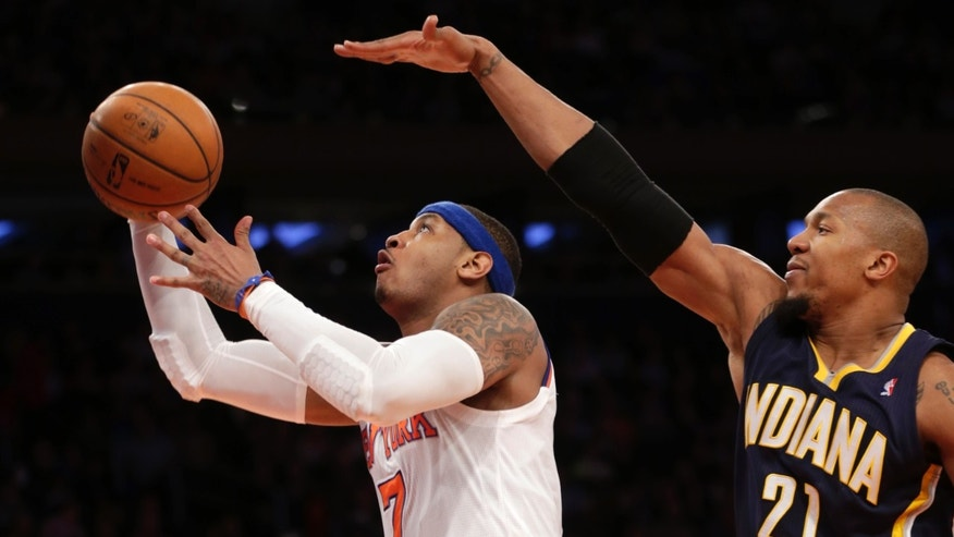 New York Knicks' Carmelo Anthony, left, shoots past Indiana Pacers' David West during the second half of the NBA basketball game, Sunday, April 14, 2013, in New York. The Knicks won 90-80. (AP Photo/Seth Wenig)