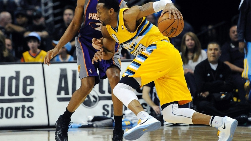Denver Nuggets guard Andre Iguodala, right, tries to drive past Phoenix Suns forward Wesley Johnson, left, in the first quarter of an NBA basketball game on Wednesday, April 17, 2013, in Denver. (AP Photo/Chris Schneider)
