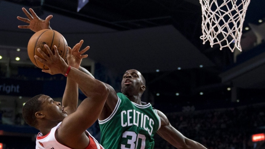Toronto Raptors guard Kyle Lowry (3) tries to shoot under pressure from Boston Celtics forward Brandon Bass (30) during first-half NBA basketball game action in Toronto, Wednesday April 17, 2013. (AP photo/The Canadian Press, Frank Gunn)