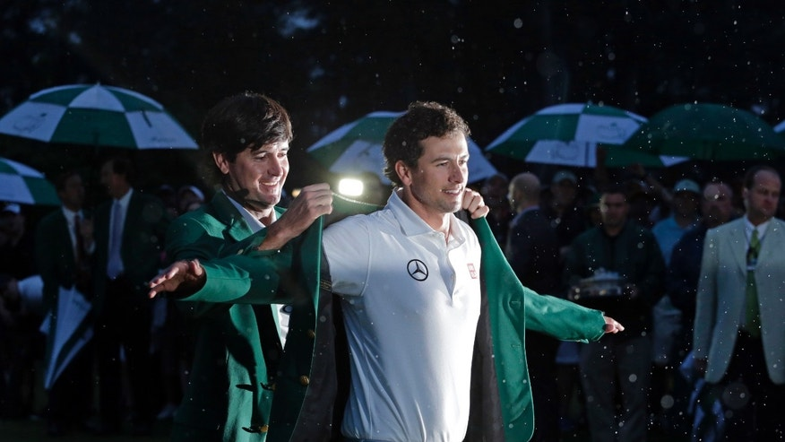 Bubba Watson, left, helps Adam Scott, of Australia, put on his green jacket after winning the Masters golf tournament Sunday, April 14, 2013, in Augusta, Ga. (AP Photo/Charlie Riedel)