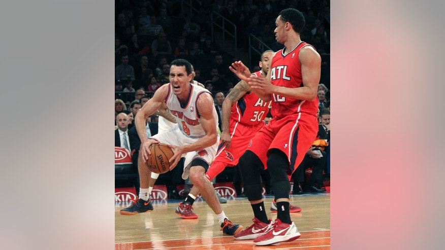 New York Knicks' Pablo Prigioni (9) grimaces as he injures his foot driving past Dahntay Jones (30) and Atlanta Hawks' John Jenkins during the first half of an NBA basketball game, Wednesday, April 17, 2013, at Madison Square Garden in New York.  (AP Photo/Mary Altaffer)