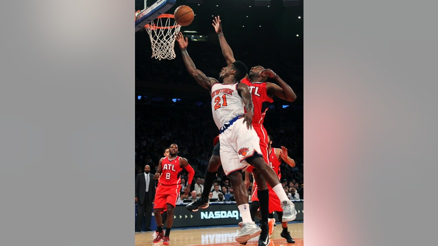 New York Knicks' Iman Shumpert (21) shoots past Atlanta Hawks' Anthony Tolliver during the first half of an NBA basketball game, Wednesday, April 17, 2013, at Madison Square Garden in New York. (AP Photo/Mary Altaffer)