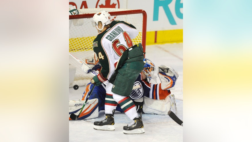 Minnesota Wild's Mikael Granlund, 64, scores on the Edmonton Oilers goalie Devan Dubnyk during second period NHL hockey action in Edmonton, Alberta, on Tuesday, April 16, 2013.  (AP Photo/The Canadian Press, John Ulan)