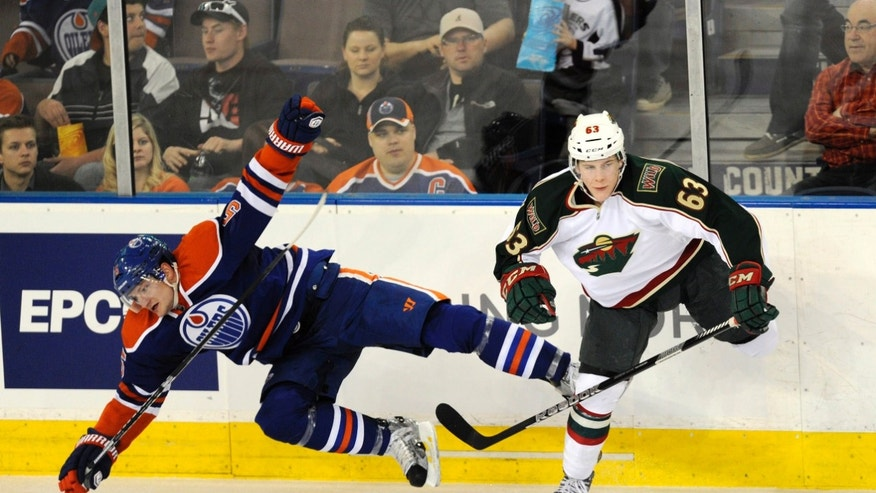 Minnesota Wild's Charlie Coyle, right, checks the Edmonton Oilers' Ladislav Smid during second period NHL hockey game action in Edmonton, Alberta, on Tuesday, April 16, 2013.  (AP Photo/The Canadian Press, John Ulan)