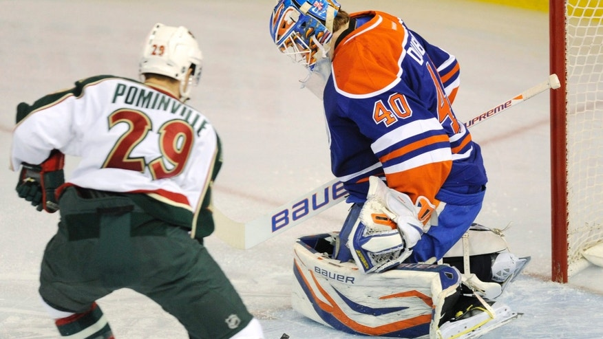 Minnesota Wild's Jason Pominville (29) watches the shot from teammate Kyle Brodziak (not shown) score pass Edmonton Oilers goalie Devan Dubnyk (40) during first period NHL hockey game action in Edmonton,Alberta, on Tuesday, April 16, 2013.  (AP Photo/The Canadian Press, John Ulan)