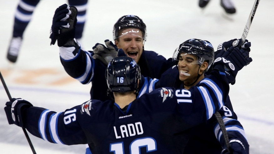 Winnipeg Jets' Blake Wheeler, top, and Evander Kane (9) celebrate with Andrew Ladd (16) after he scored the winning goal against the Tampa Bay Lightning during the shootout of their NHL hockey game in Winnipeg, Manitoba, Tuesday, April 16, 2013. The Jets won 4-3. (AP Photo/The Canadian Press, Trevor Hagan)