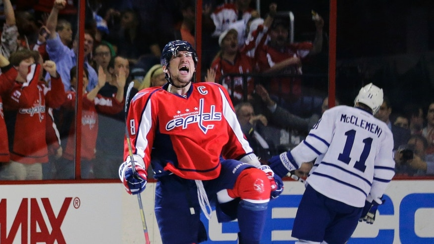 Washington Capitals left wing Alex Ovechkin (8), from Russia, celebrates his goal as Toronto Maple Leafs center Jay McClement (11) skates behind in the second period of an NHL hockey game Tuesday, April 16, 2013 in Washington. (AP Photo/Alex Brandon)