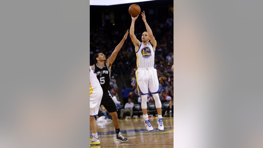 Golden State Warriors' Stephen Curry (30) makes a three-point basket next to San Antonio Spurs' Cory Joseph (5) during the second half of an NBA basketball game in Oakland, Calif., Monday, April 15, 2013. Golden State won 116-106.   (AP Photo/Marcio Jose Sanchez)