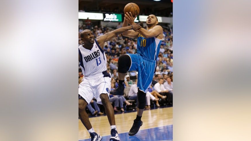 New Orleans Hornets guard Eric Gordon (10) shoots against Dallas Mavericks guard Mike James (13) during the second half of an NBA basketball game in Dallas, Wednesday April 17, 2013. Dallas won 99-87. (AP Photo/Mike Fuentes)