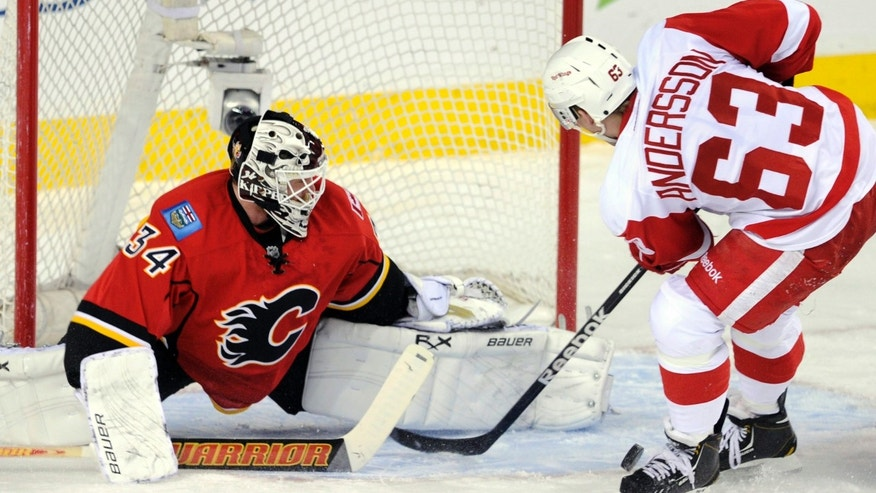 Detroit Red Wings' Joakim Andersson, right, of Sweden, has a shot stopped by Calgary Flames goalie Miikka Kiprusoff, of Finland, during the first period of their NHL hockey game in Calgary, Alberta, Wednesday, April 17, 2013. (AP Photo/The Canadian Press, Larry MacDougal)