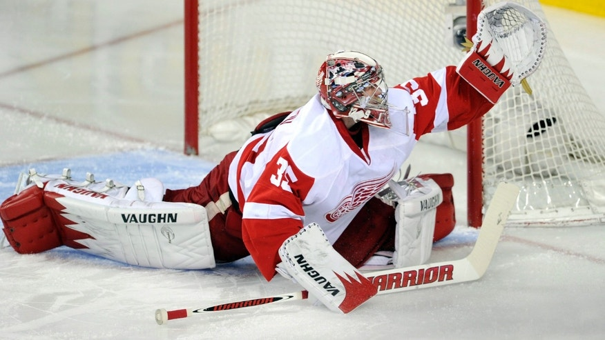 Detroit Red Wings goalie Jimmy Howard makes a save against the Calgary Flames during the first period of their NHL hockey game in Calgary, Alberta, Wednesday, April 17, 2013. (AP Photo/The Canadian Press, Larry MacDougal)
