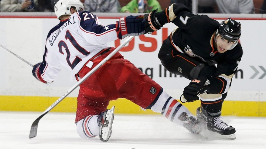 Anaheim Ducks center Andrew Cogliano, right, knocks the puck away from Columbus Blue Jackets defenseman James Wisniewski during the second period of an NHL hockey game in Anaheim, Calif., Wednesday, April 17, 2013. (AP Photo/Chris Carlson)
