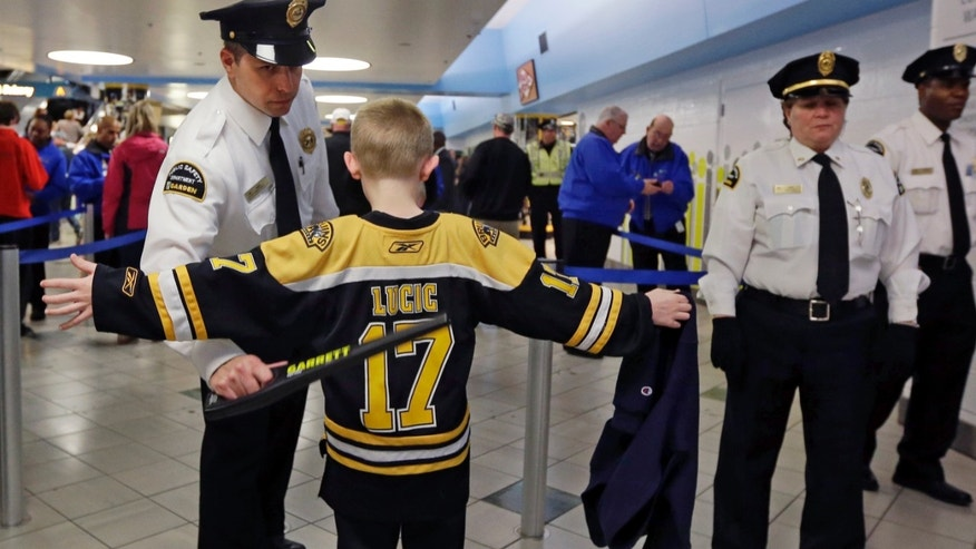 A young Boston Bruins fan raises his arms to be checked on the way into TD Garden prior to a Bruins NHL hockey game against the Buffalo Sabres in Boston, Wednesday, April 17, 2013, in the aftermath of Monday's Boston Marathon bombings. (AP Photo/Elise Amendola)