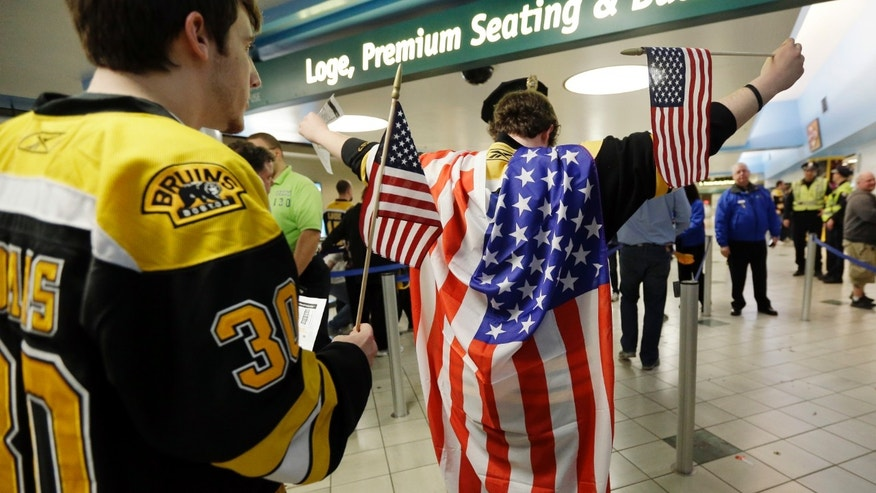 A fan wearing a United States flag raises his arms to be checked on the way into TD Garden prior to a Boston Bruins hockey game in Boston, Wednesday, April 17, 2013, in the aftermath of Monday's Boston Marathon bombings. (AP Photo/Elise Amendola)