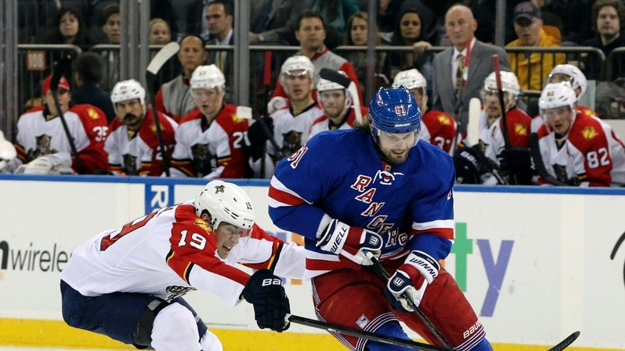 CORRECTS ID TO RICK NASH- Florida Panthers' Scottie Upshall (19) battles for the puck against New York Rangers' Rick Nash during the second period of an NHL hockey game Thursday, April 18, 2013 at Madison Square Garden in New York. (AP Photo/Mary Altaffer)