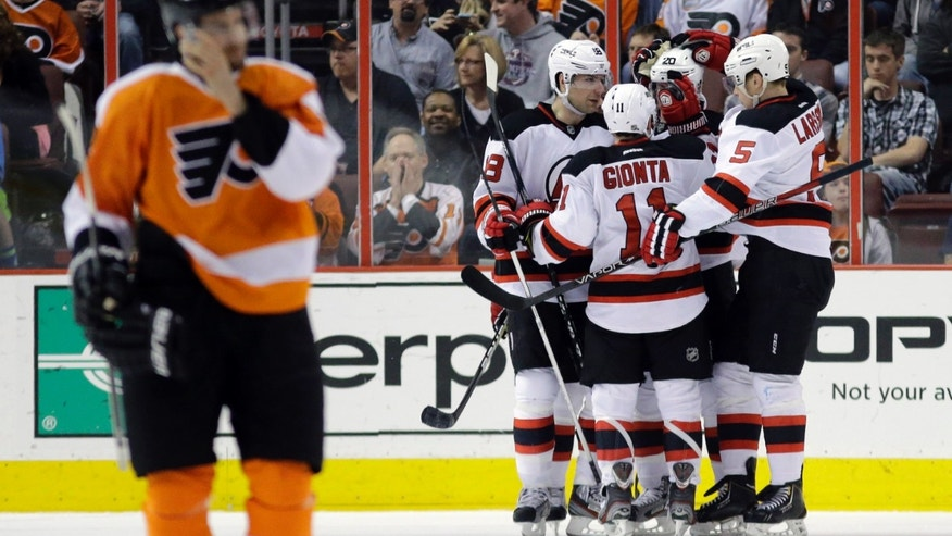New Jersey Devils' Adam Larsson (5), of Sweden, Ryan Carter (20), Stephen Gionta (11) and Steve Bernier (18) celebrate after a goal by Carter as Philadelphia Flyers' Simon Gagne skates back to the bench during the second period of an NHL hockey game, Thursday, April 18, 2013, in Philadelphia. (AP Photo/Matt Slocum)