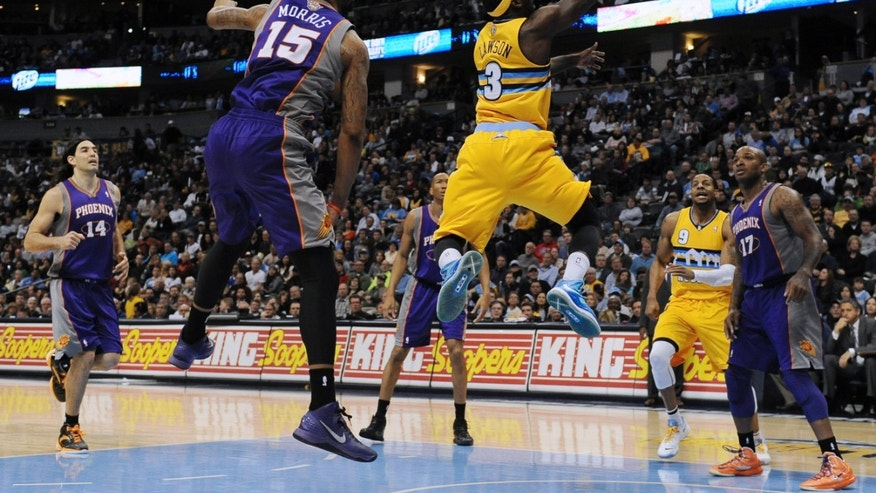 Denver Nuggets guard Ty Lawson, center, drives to the basket past Phoenix Suns forward Marcus Morris, left, in the second half of an NBA basketball game on Wednesday, April 17, 2013, in Denver. The Nuggets won 118-98. (AP Photo/Chris Schneider)