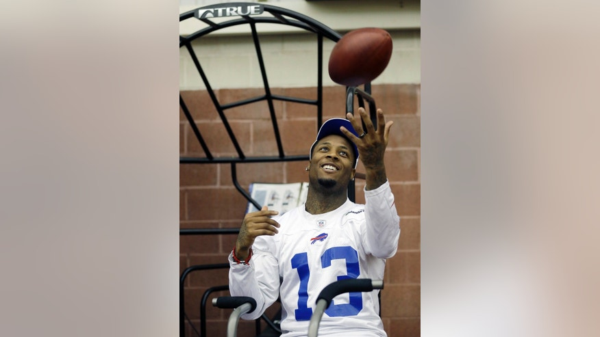 Buffalo Bills' Stevie Johnson tosses a football while riding an exercise bike during NFL football minicamp in Orchard Park, N.Y., Thursday, April 18, 2013. (AP Photo/David Duprey)