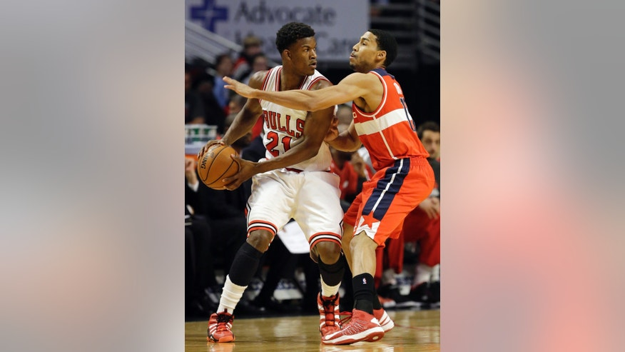 Chicago Bulls guard Jimmy Butler, left, looks to pass as Washington Wizards guard Garrett Temple defends during the first half of an NBA basketball game in Chicago, Wednesday, April 17, 2013. (AP Photo/Nam Y. Huh)