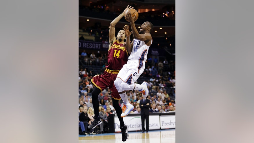 Charlotte Bobcats' Kemba Walker (15) drives past Cleveland Cavaliers' Shaun Livingston (14) during the first half of an NBA basketball game in Charlotte, N.C., Wednesday, April 17, 2013. (AP Photo/Chuck Burton)