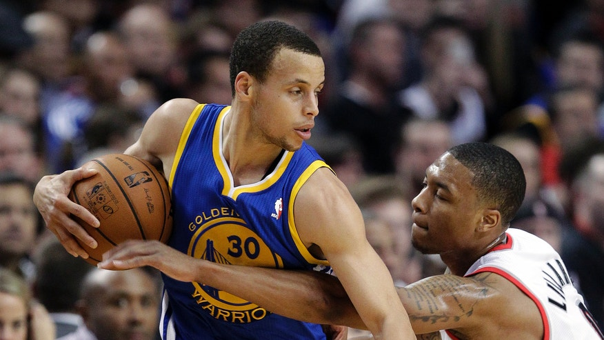 Portland Trail Blazers guard Damian Lillard, right, reaches in on Golden State Warriors guard Stephen Curry during the first quarter of an NBA basketball game in Portland, Ore., Wednesday, April 17, 2013. (AP Photo/Don Ryan)