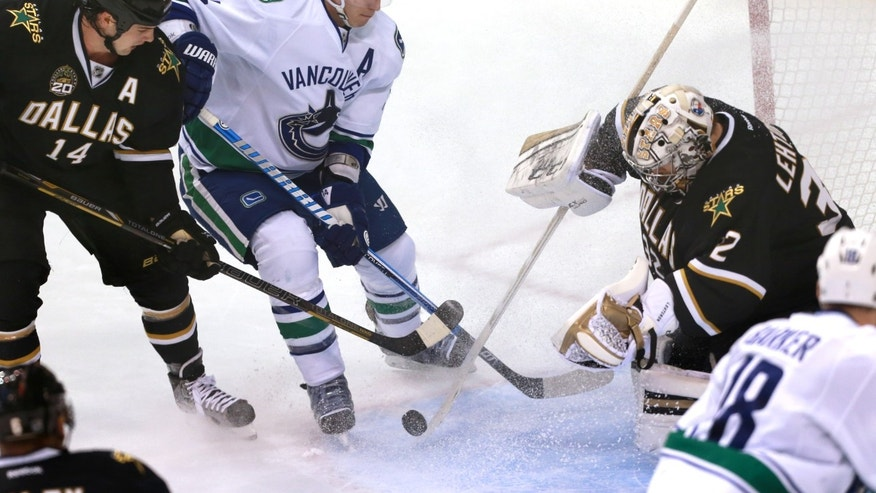 Vancouver Canucks center Alex Burrows (14) attempts a shot on Dallas Stars goalie Kari Lehtonen (32) as Stars' Jamie Benn (14) defends during the second period of an NHL hockey game on Thursday, April 18, 2013, in Dallas. (AP Photo/ Michael Mulvey)