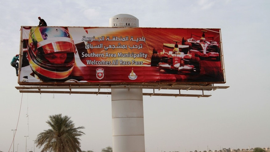 Asian workers secure a billboard welcoming Formula One fans in English and Arabic along a highway near the Bahrain International Circuit in Sakhir, Bahrain, on Wednesday, April 17, 2013. The F1 Bahrain Grand Prix will be held on Sunday. (AP Photo/Hasan Jamali)