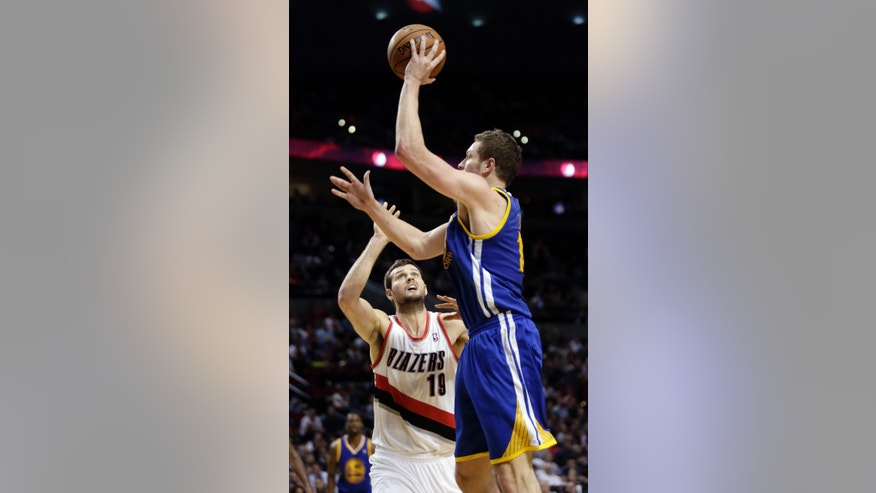 Golden State Warriors forward David Lee, right, shoots over Portland Trail Blazers forward Joel Freeland during the second half of an NBA basketball game in Portland, Ore., Wednesday, April 17, 2013.  Lee scored 20 points and pulled in 10 rebounds as the Warriors won 99-88.(AP Photo/Don Ryan)