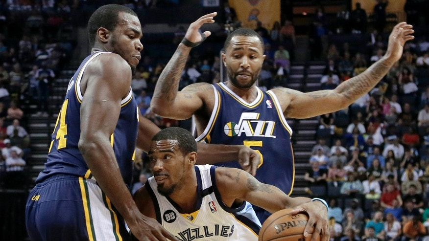 Memphis Grizzlies' Mike Conley (11) drives under Utah Jazz's Mo Williams (5) and Paul Millsap, left, during the first half of an NBA basketball game in Memphis, Tenn., Wednesday, April 17, 2013. (AP Photo/Danny Johnston)