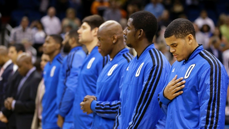 From right, Orlando Magic's Tobias Harris, Andrew Nicholson, Al Harrington, Nikola Vucevic, Kyle O'Quinn and Maurice Harkless observe a moment of silence for the victims of the Boston Marathon explosions before an NBA basketball game against the Chicago Bulls, Monday, April 15, 2013, in Orlando, Fla. (AP Photo/John Raoux)