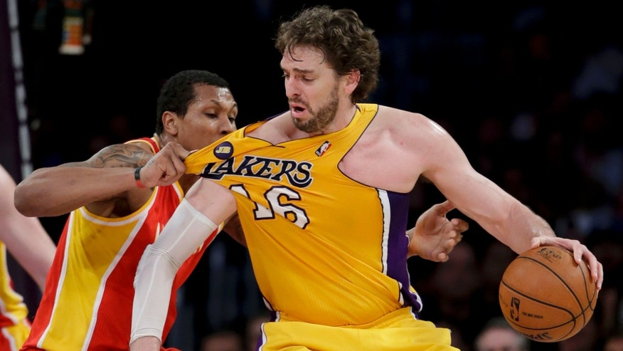 Los Angeles Lakers' Pau Gasol, right, of Spain, is fouled by Houston Rockets' Greg Smith during the second of an NBA basketball game in Los Angeles, Wednesday, April 17, 2013. The Lakers won 99-95 in overtime. (AP Photo/Jae C. Hong)