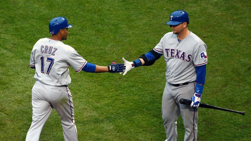 Texas Rangers' A.J. Pierzynski, right, greets Nelson Cruz after Cruz's home run off Chicago Cubs starting pitcher Carlos Villanueva during the seventh inning of a baseball game Thursday, April 18 2013, in Chicago. The Cubs won 6-2. (AP Photo/Charles Rex Arbogast)