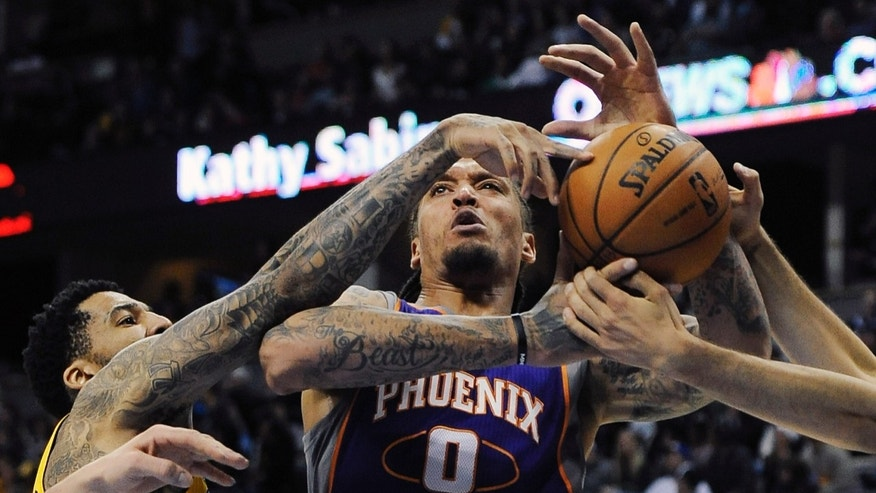Denver Nuggets guard Wilson Chandler, left, tangles with Phoenix Suns forward Michael Beasley, center, in the second half of an NBA basketball game on Wednesday, April 17, 2013, in Denver. The Nuggets won 118-98. (AP Photo/Chris Schneider)