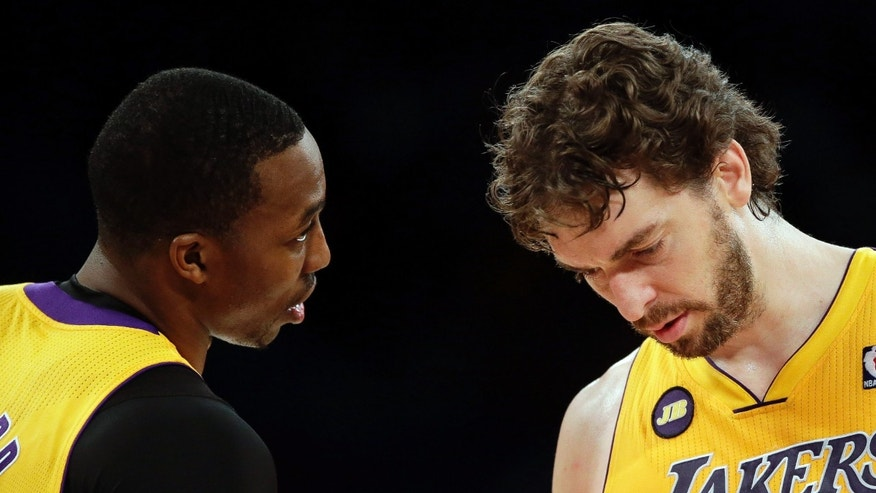 Los Angeles Lakers' Dwight Howard, left, talks to Pau Gasol, of Spain, during the first half of an NBA basketball game against the Houston Rockets in Los Angeles, Wednesday, April 17, 2013. (AP Photo/Jae C. Hong)