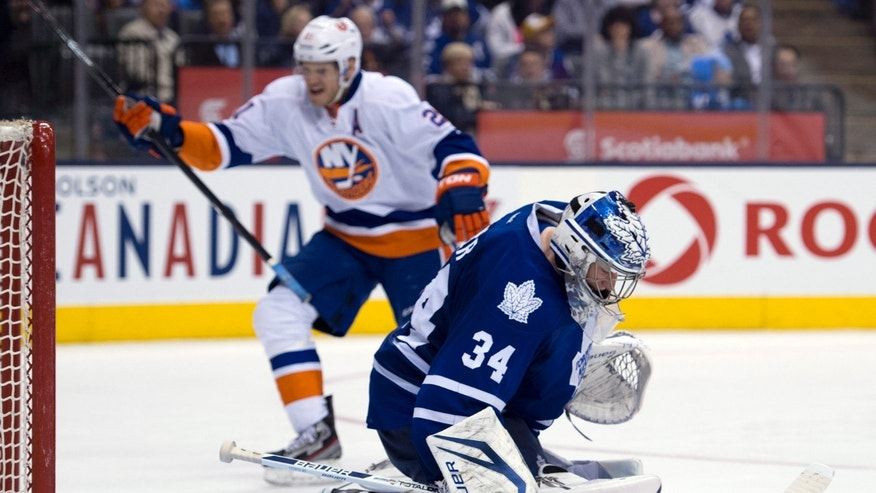 Toronto Maple Leafs goaltender James Reimer (34) reacts as New York Islanders Kyle Okposo, background, celebrates his team's fifth goal of an NHL hockey game during the third period in Toronto, Thursday, April 18, 2013. (AP photo/The Canadian Press, Frank Gunn)