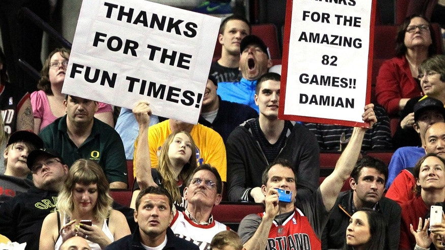 Portland Trail Blazers fans hold up signs in the final moments of an NBA basketball game against the Golden State Warriors in Portland, Ore., Wednesday, April 17, 2013.  The Warriors won 99-88.(AP Photo/Don Ryan)