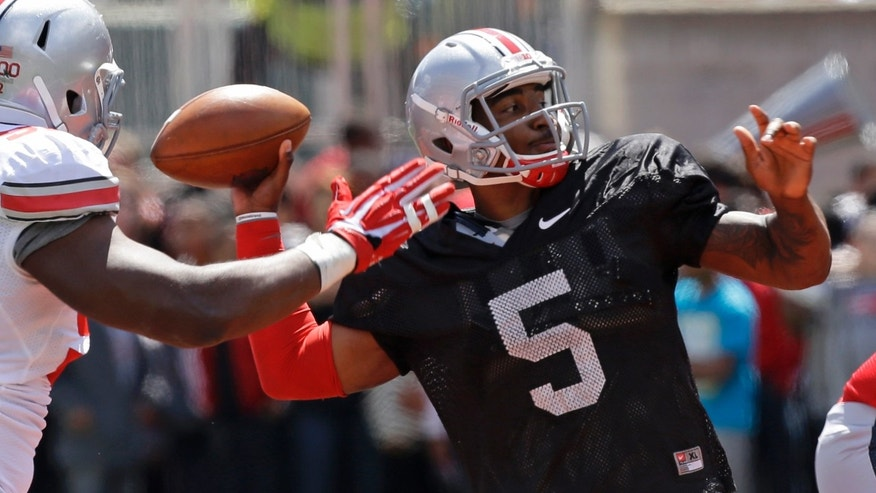 Scarlet quarterback Braxton Miller (5) passes under pressure from Grey defensive lineman Adolphus Washington during Ohio State's annual spring NCAA college football game, Saturday, April 13, 2013, in Cincinnati. (AP Photo/Al Behrman)