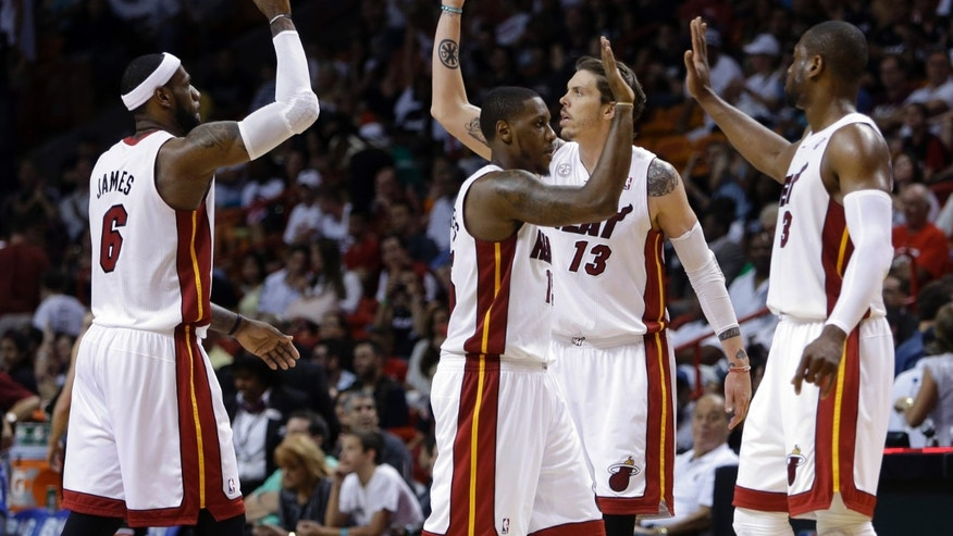Miami Heat's LeBron James (6), Mike Miller (13), Mario Chalmers, center, and Dwyane Wade (3) high-five after taking a ten-point lead over the Chicago Bulls during the second half of an NBA basketball game on Sunday, April 14, 2013, in Miami. The Heat defeated the Bulls 105-93. (AP Photo/Lynne Sladky)