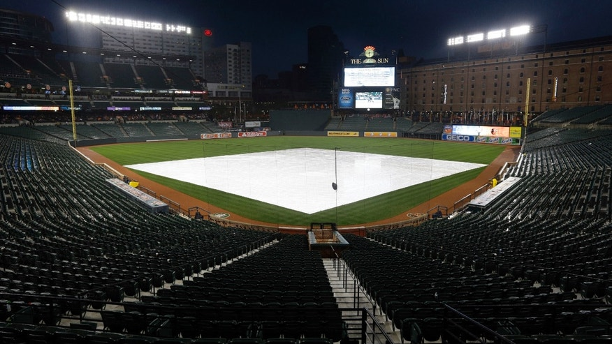The infield is covered by a tarp at Oriole Park at Camden Yards as rain falls before an interleague baseball game between the Los Angeles Dodgers and the Baltimore Orioles on Friday, April 19, 2013, in Baltimore. (AP Photo/Patrick Semansky)
