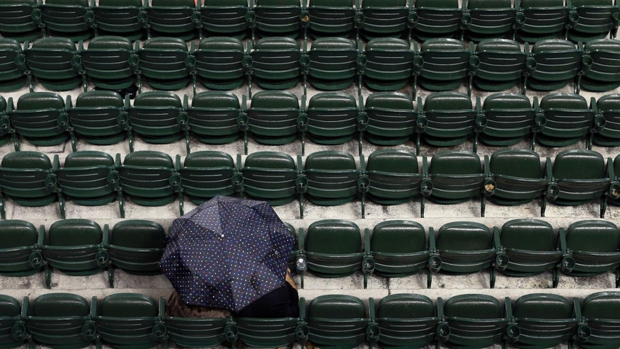 Fans take cover underneath an umbrella as rain falls before an interleague baseball game between the Los Angeles Dodgers and the Baltimore Orioles on Friday, April 19, 2013, in Baltimore. (AP Photo/Patrick Semansky)
