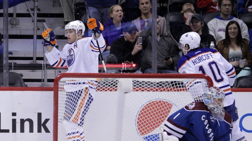 Edmonton Oilers left wing Taylor Hall raises his arms after scoring a goal against Colorado Avalanche goalie Semyon Varlamov (1) in the first period of an NHL game on Friday, April 19, 2013, in Denver. Oilers center Shawn Horcoff (10) skates to Hall. (AP Photo/Joe Mahoney)