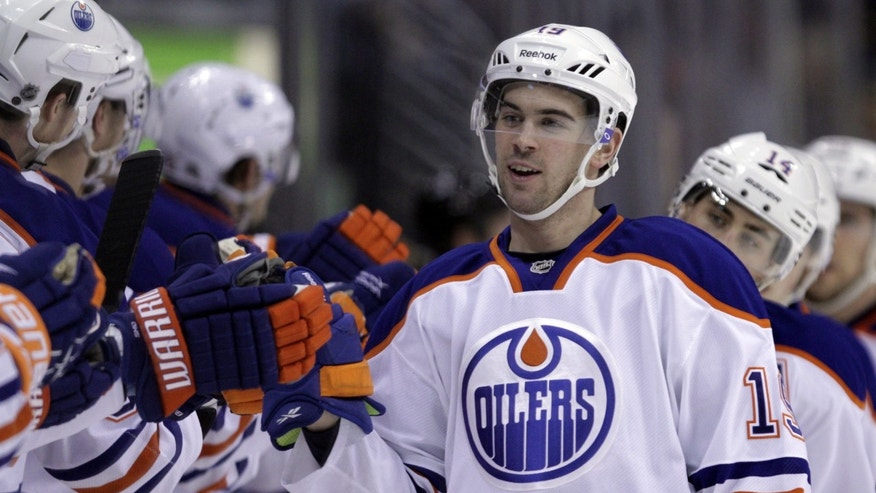 Edmonton Oilers players congratulate Edmonton Oilers center Jordan Eberle (14) after his goal against the Colorado Avalanche in the first period of an NHL game on Friday, April 19, 2013, in Denver. (AP Photo/Joe Mahoney)