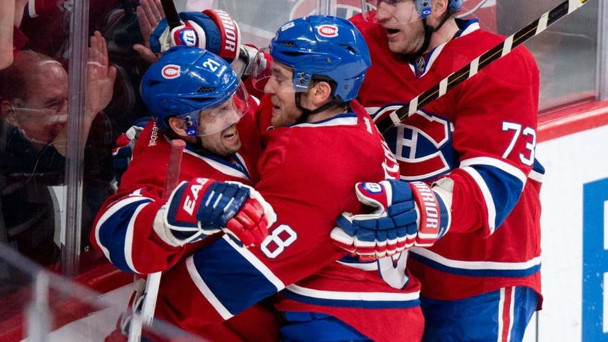 Montreal Canadiens' Brian Gionta, left, is hugged by Yannick Weber, center, and Michael Ryder following a power-play goal against the Tampa Bay Lightning during the third period of their NHL hockey game, Thursday, April 18, 2013, in Montreal. The Canadiens won 3-2. (AP Photo/The Canadian Press, Paul Chiasson)