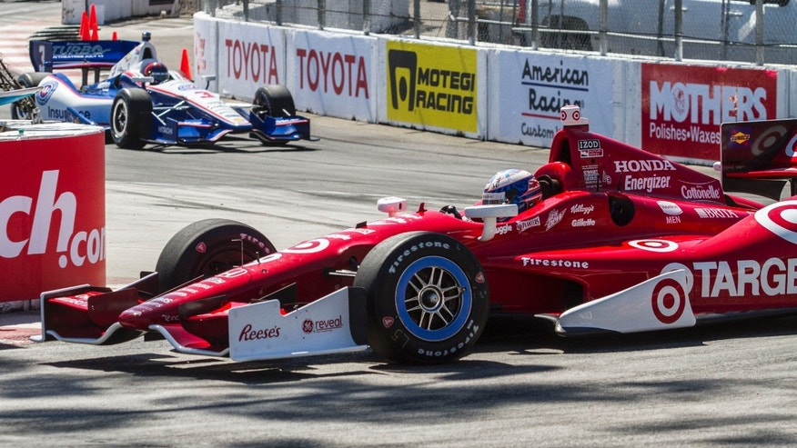 Driver Scott Dixon, front, is followed by Helio Castroneves (3) during the practice for the IndyCar Grand Prix of Long Beach auto race Friday, April 19, 2013, in Long Beach, Calif. (AP Photo/Ringo H.W. Chiu)