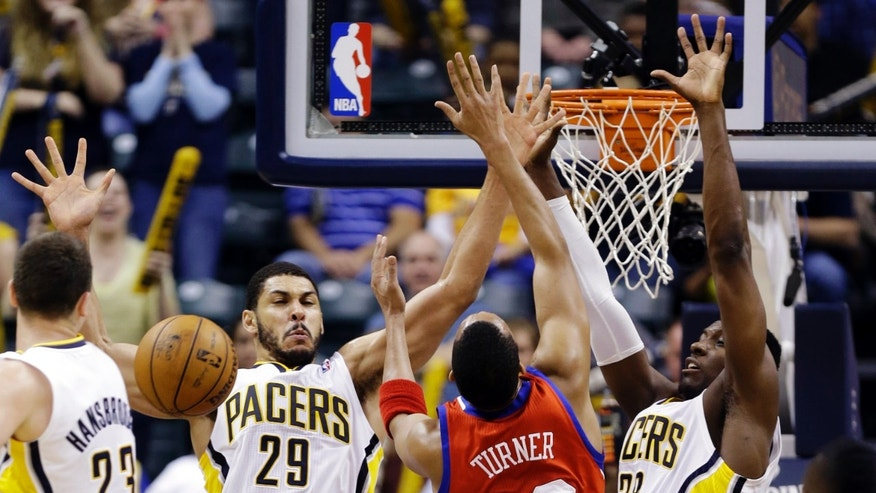 Philadelphia 76ers forward Evan Turner (12) is fouled as he shoots over Indiana Pacers forward Jeff Pendergraph (29) and center Ian Mahinmi in the second half of an NBA basketball game in Indianapolis, Wednesday, April 17, 2013. The 76ers won 105-95. (AP Photo/Michael Conroy)
