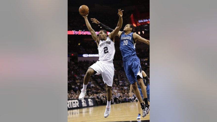 San Antonio Spurs' Kawhi Leonard (2) shoots around Minnesota Timberwolves' Chris Johnson (20) during the first half of an NBA basketball game on Wednesday, April 17, 2013, in San Antonio. (AP Photo/Eric Gay)