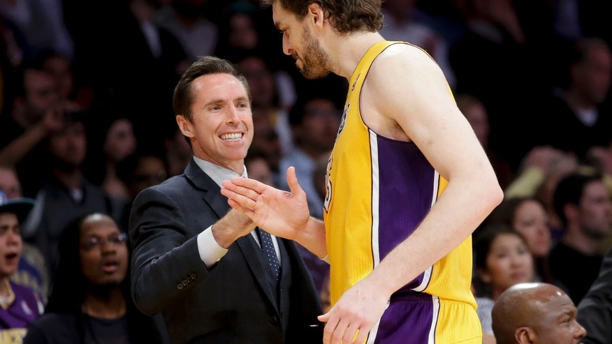 Los Angeles Lakers' Pau Gasol, of Spain, is greeted by Steve Nash during overtime of an NBA basketball game against the Houston Rockets in Los Angeles, Wednesday, April 17, 2013. The Lakers won 99-95. (AP Photo/Jae C. Hong)