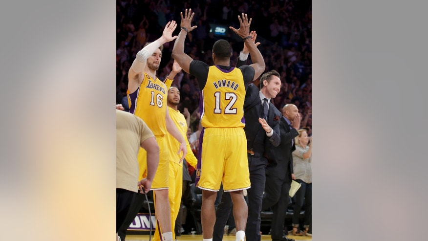 Los Angeles Lakers' Pau Gasol, left, of Spain, Dwight Howard, center, and Steve Nash celebrate their team's 99-95 overtime win against the Houston Rockets after an NBA basketball game in Los Angeles, Wednesday, April 17, 2013. (AP Photo/Jae C. Hong)