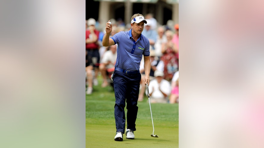 Luke Donald, of England, waves to the crowd after making birdie on the ninth green during the second round of the RBC Heritage golf tournament in Hilton Head Island, S.C., Friday, April 19, 2013. (AP Photo/Stephen Morton)